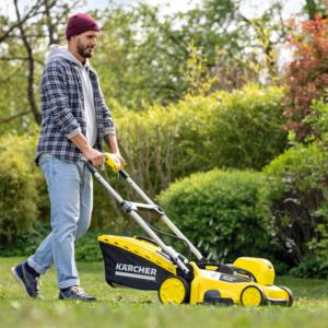 Men walking with lawn mower in garden